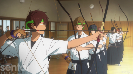 A row of archers from the Tsurune anime stand in a line at a competition, holding bows aloft in various stages of firing.
