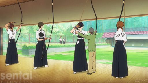 A row of young women aim kyudo bows at a row of distant targets while their teacher corrects their shooting form.