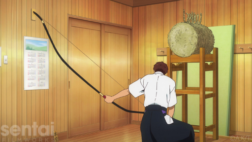A character from the Tsurune anime crouches with his back to the viewer. He holds a long kyudo bow, showing its asymmetrical structure.