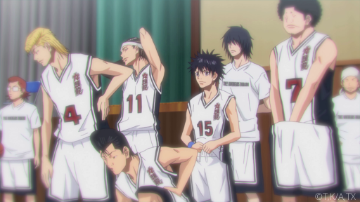 The basketball team of Kuzu High stands at attention in their white uniforms with red numbers of the front.